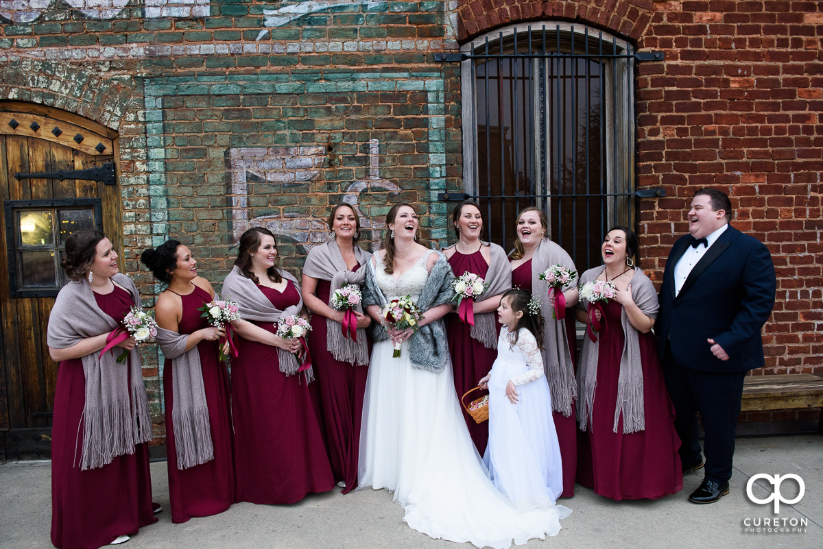 Bridesmaids and the bride laughing outside.