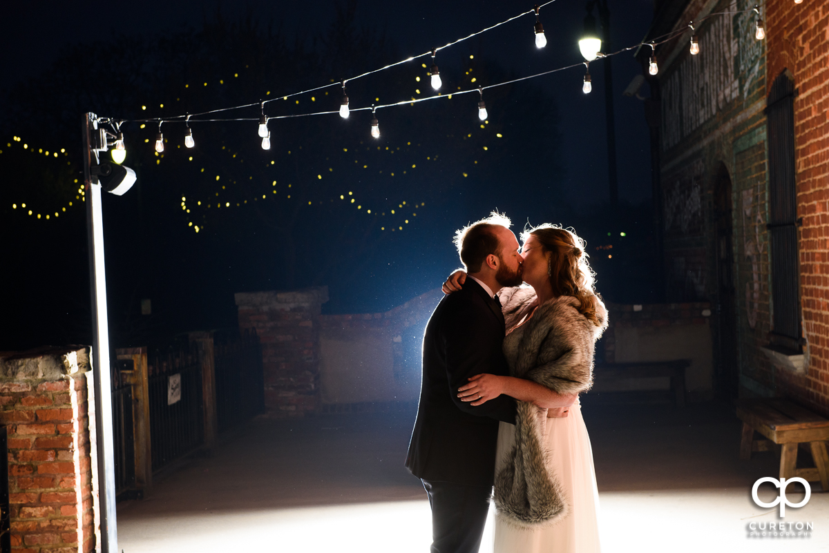 Bride and groom dancing underneath twinkly lights on the deck of the old cigar warehouse.