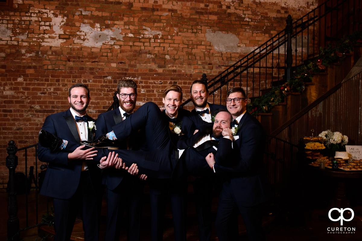 Groomsman holding up the groom.