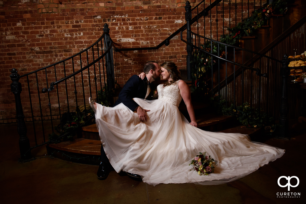 Bride and groom in an epic pose on the staircase at the old cigar warehouse.