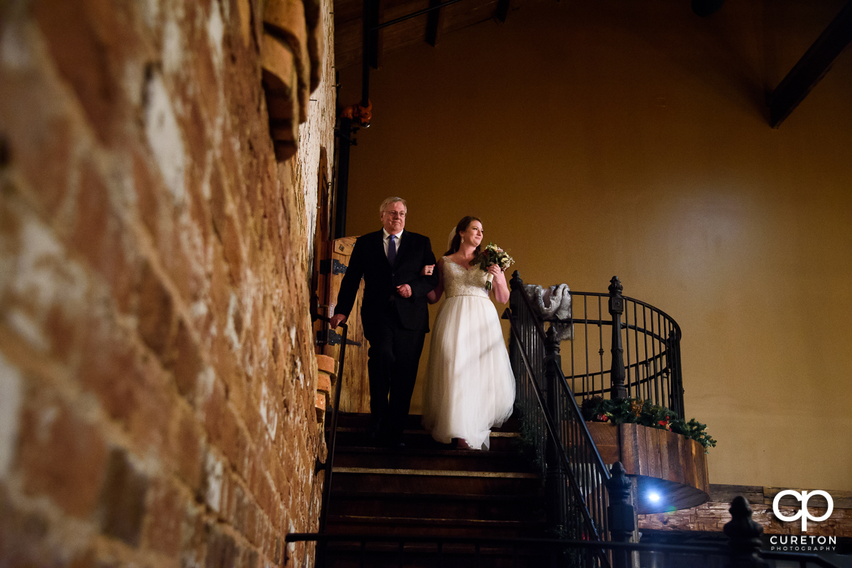 Bride and her father walking down the staircase at their wedding.
