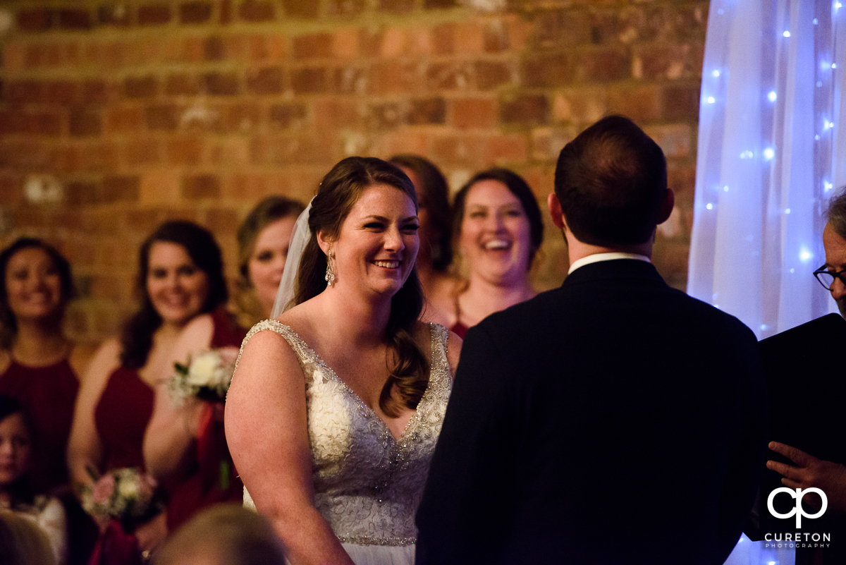 Bride laughing at her groom during the ceremony.