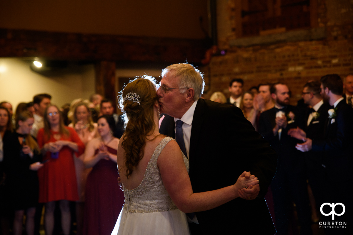 Bride's father kissing his daughter on the cheek.