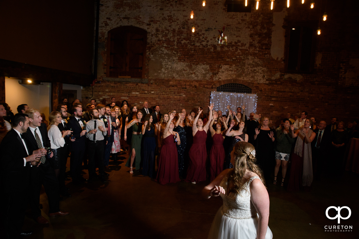 Bride tossing her bouquet at The Old Cigar Warehouse wedding reception.