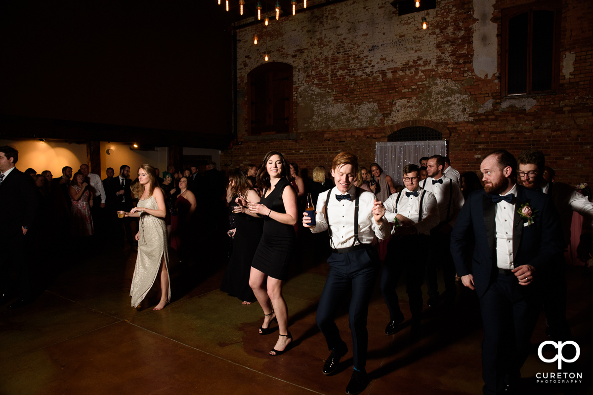 Wedding guests line dancing.