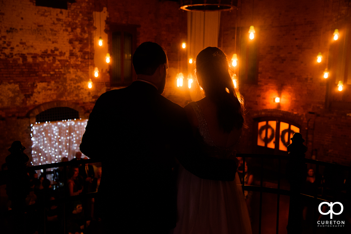 Bride and groom looking over their reception at The Old Cigar Warehouse.