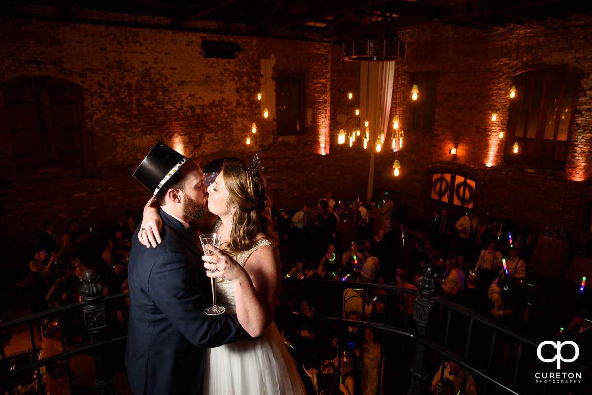Bride and groom sharing a New Years Eve kiss at their wedding.
