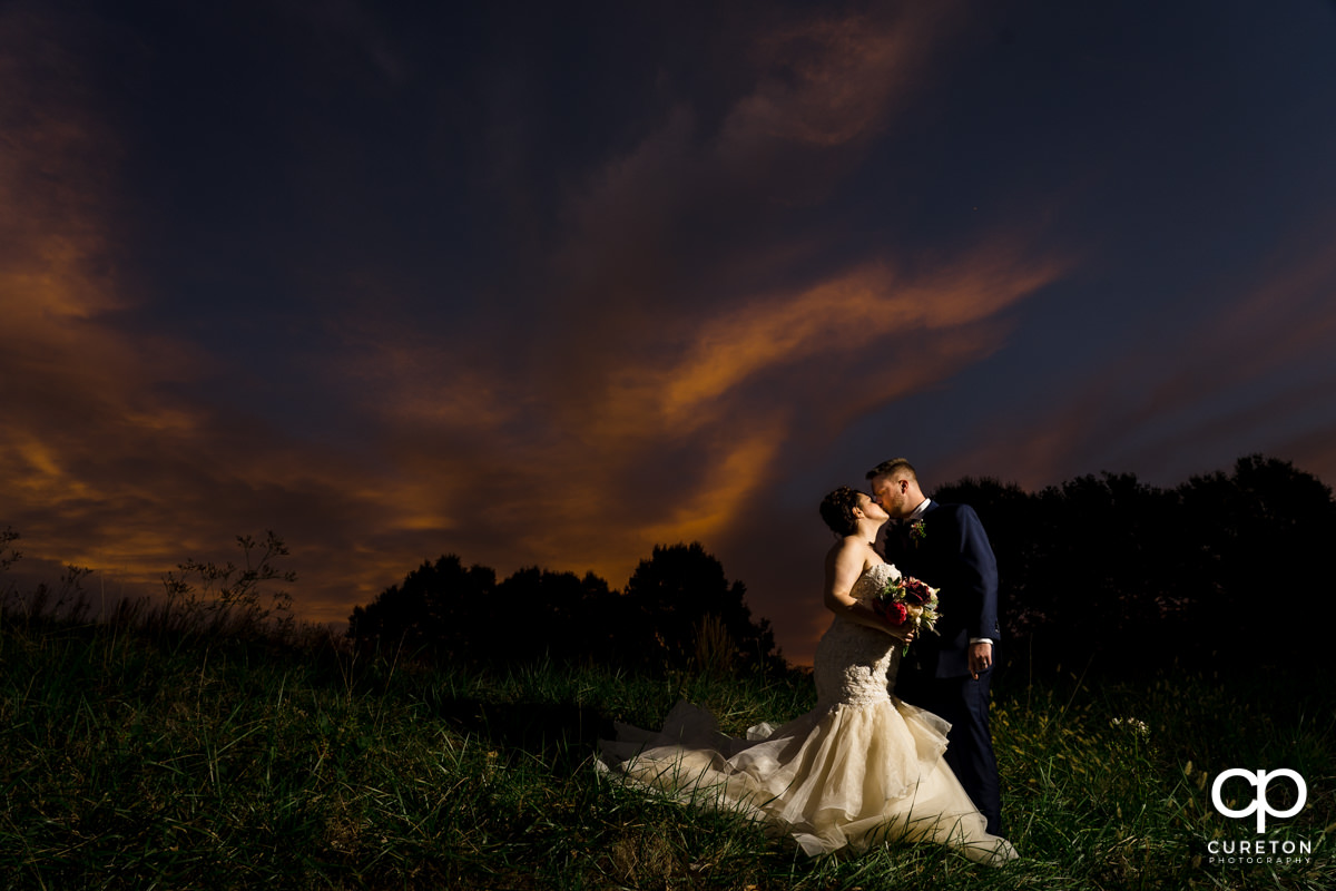 Bride and groom kissing at sunset after their Noah's Event Venue wedding.