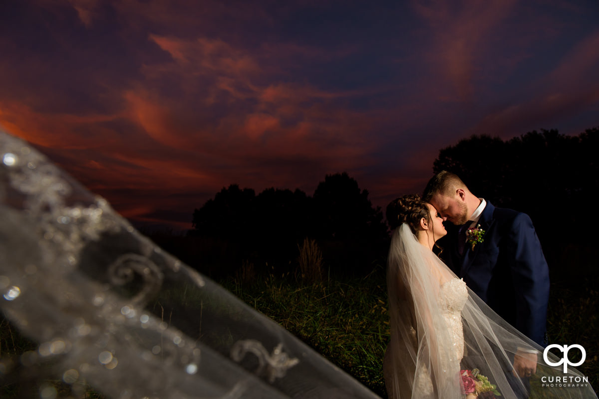 Bride and groom cuddling at sunset while her veil blows in the wind at Noah's Event Venue in Mauldin,SC.