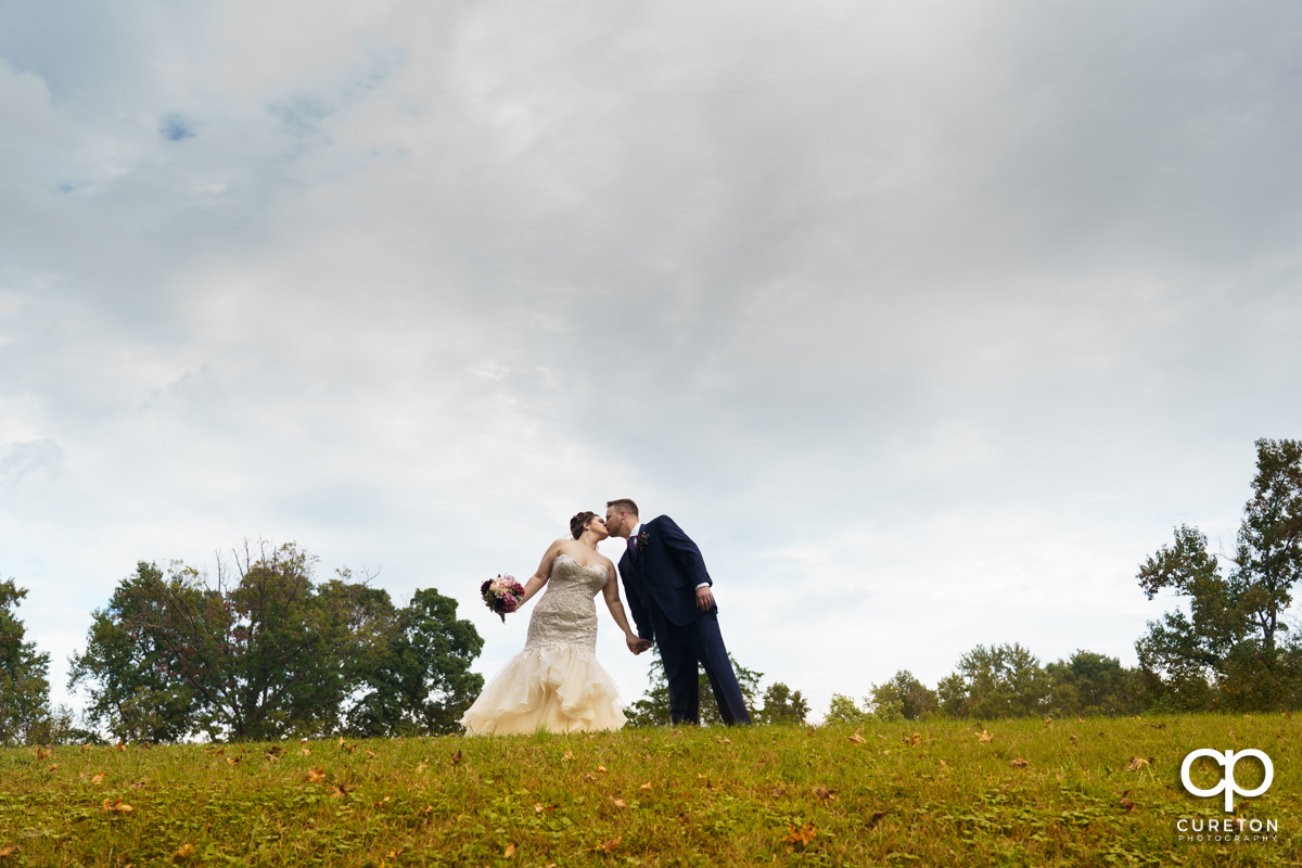 Bride and groom kissing in a field behind Noah's Event Venue in Mauldin,SC.