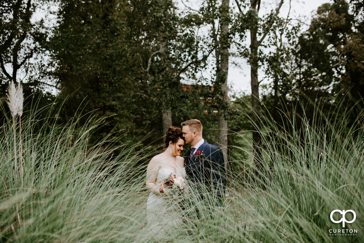 Groom and bride standing in some tall grass behind Noah's Event Venue in Mauldin,SC.