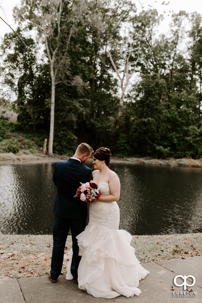 Bride and groom standing by a pond before their wedding ceremony.