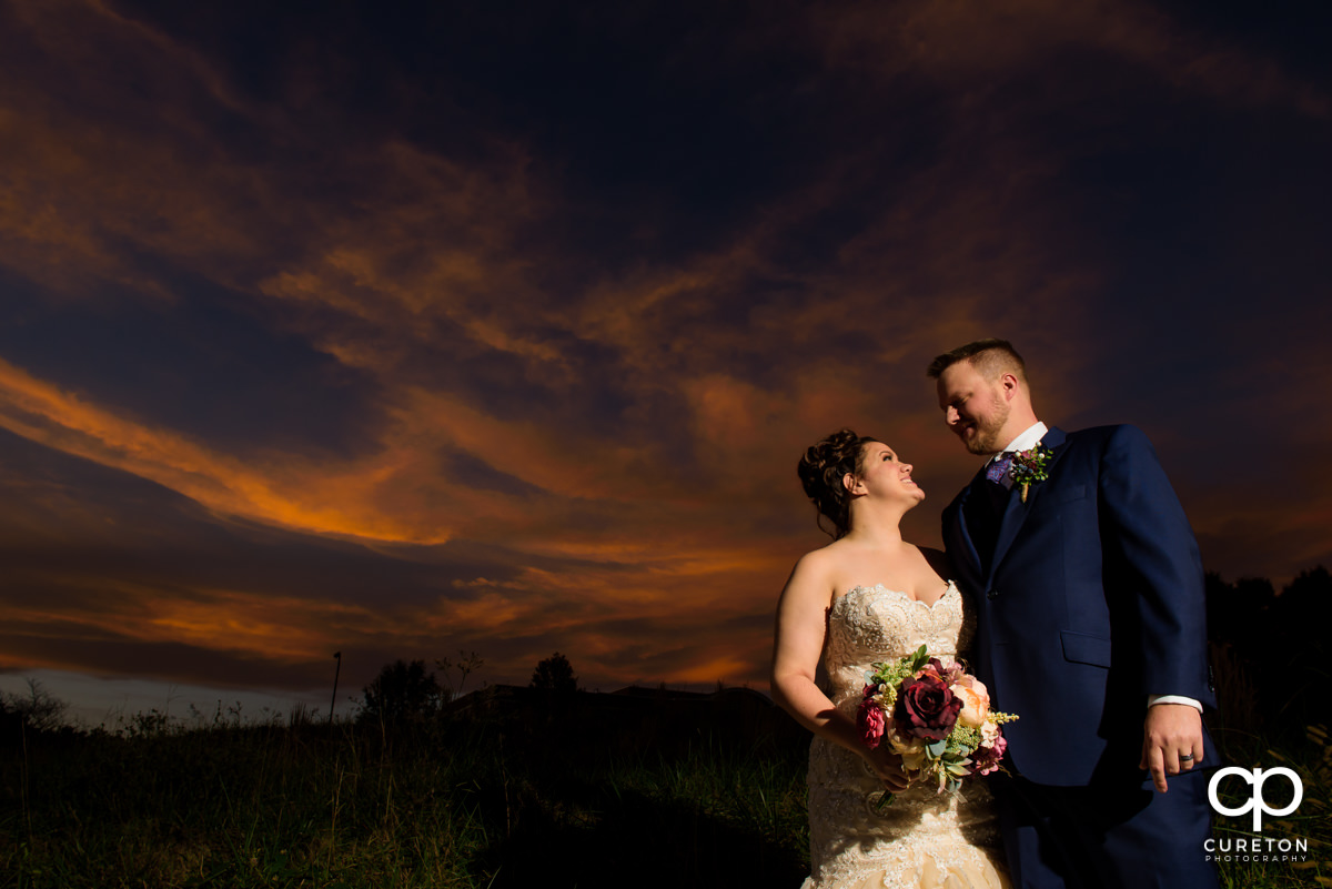 Bride and groom looking at each other at sunset at their Noah's Event Venue wedding.