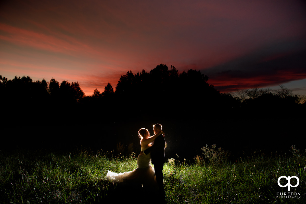 Bride and groom standing in a field after their wedding reception at Noah's Event Venue in Mauldin,SC.