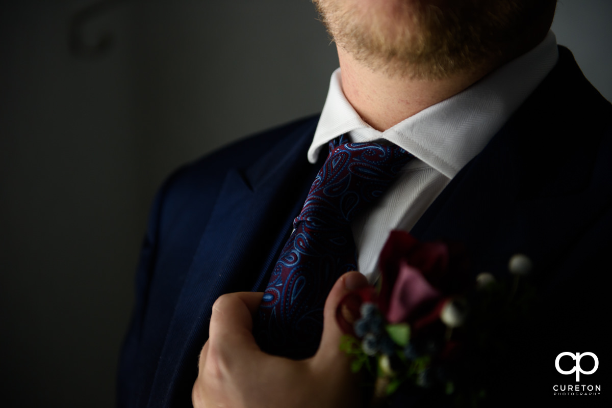 Groom holding his tie before the wedding.