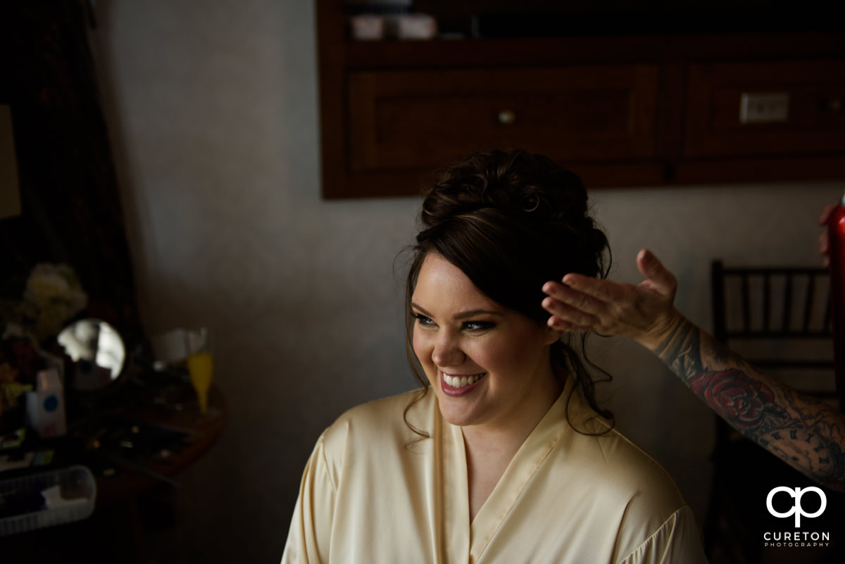 Bride having her hair done on her wedding day.