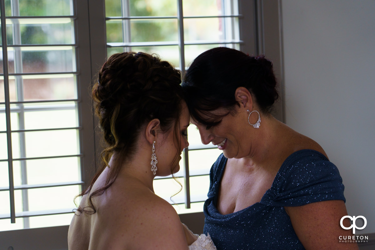 Bride and her mom sharing a moment before her wedding ceremony.
