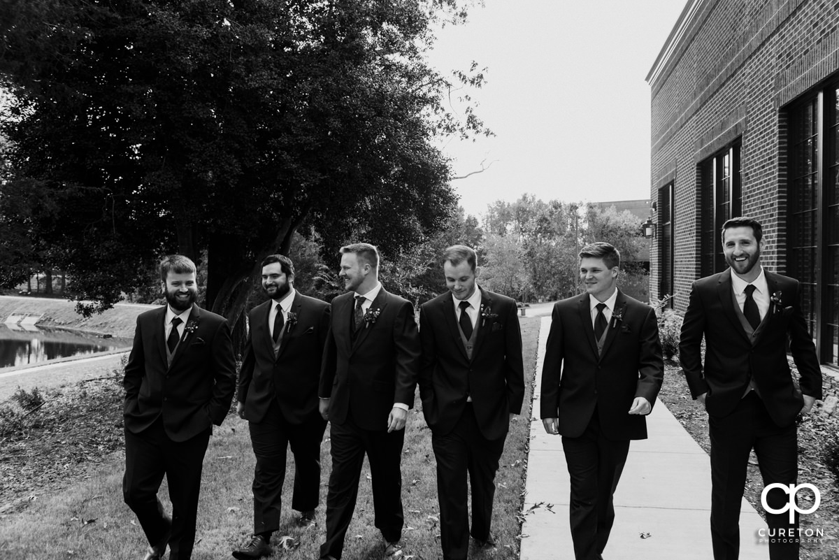 Groomsmen walking down a path together.