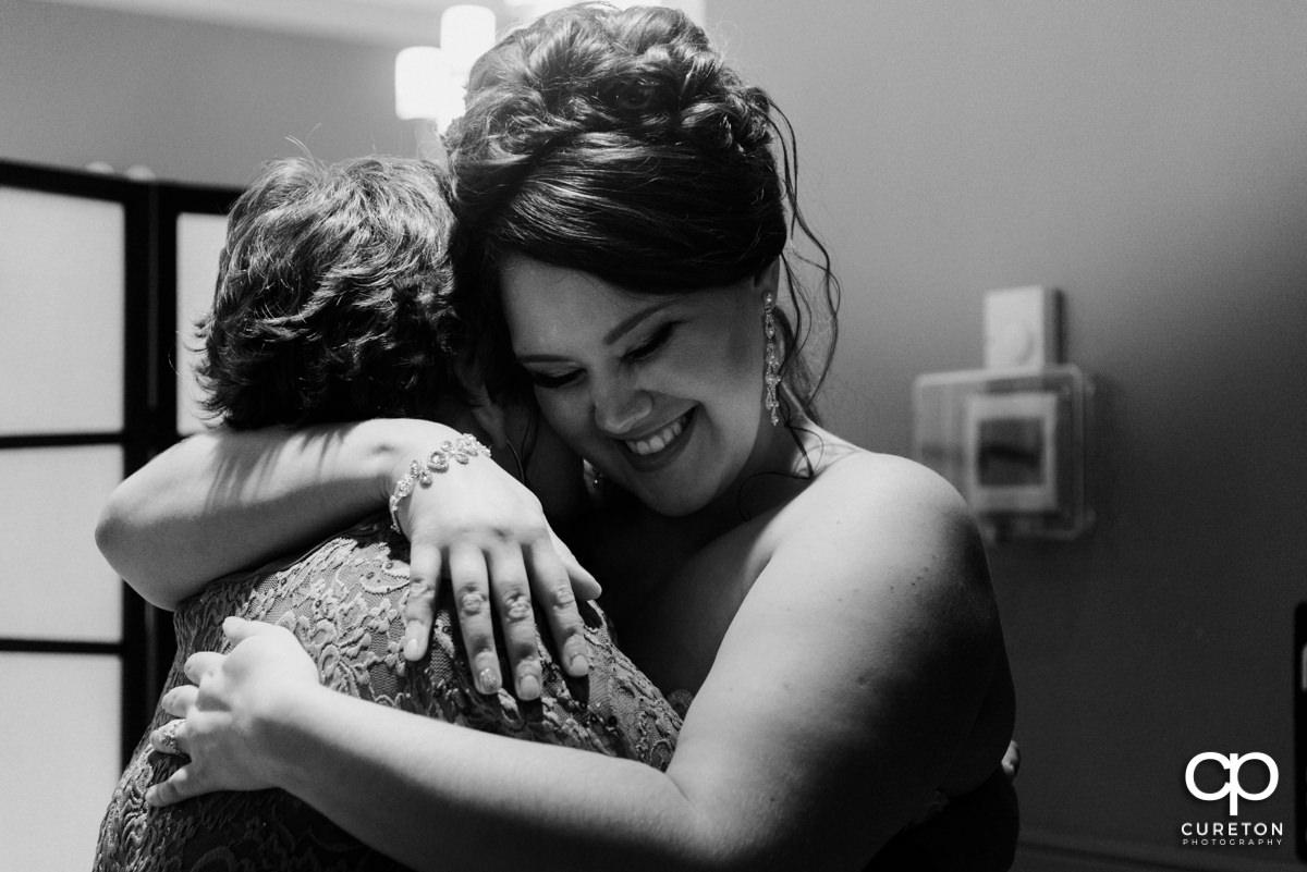 Bride hugging a family member.