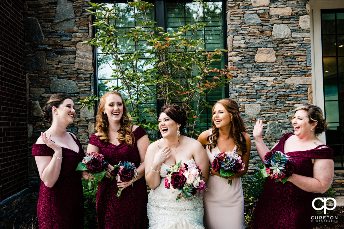 Bride laughing with her bridesmaids before her wedding in Mauldin,SC.