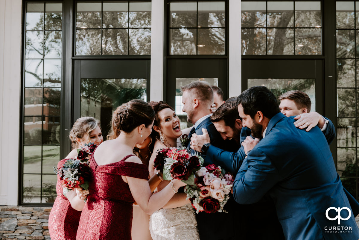 Entire wedding party hugging the bride and groom.