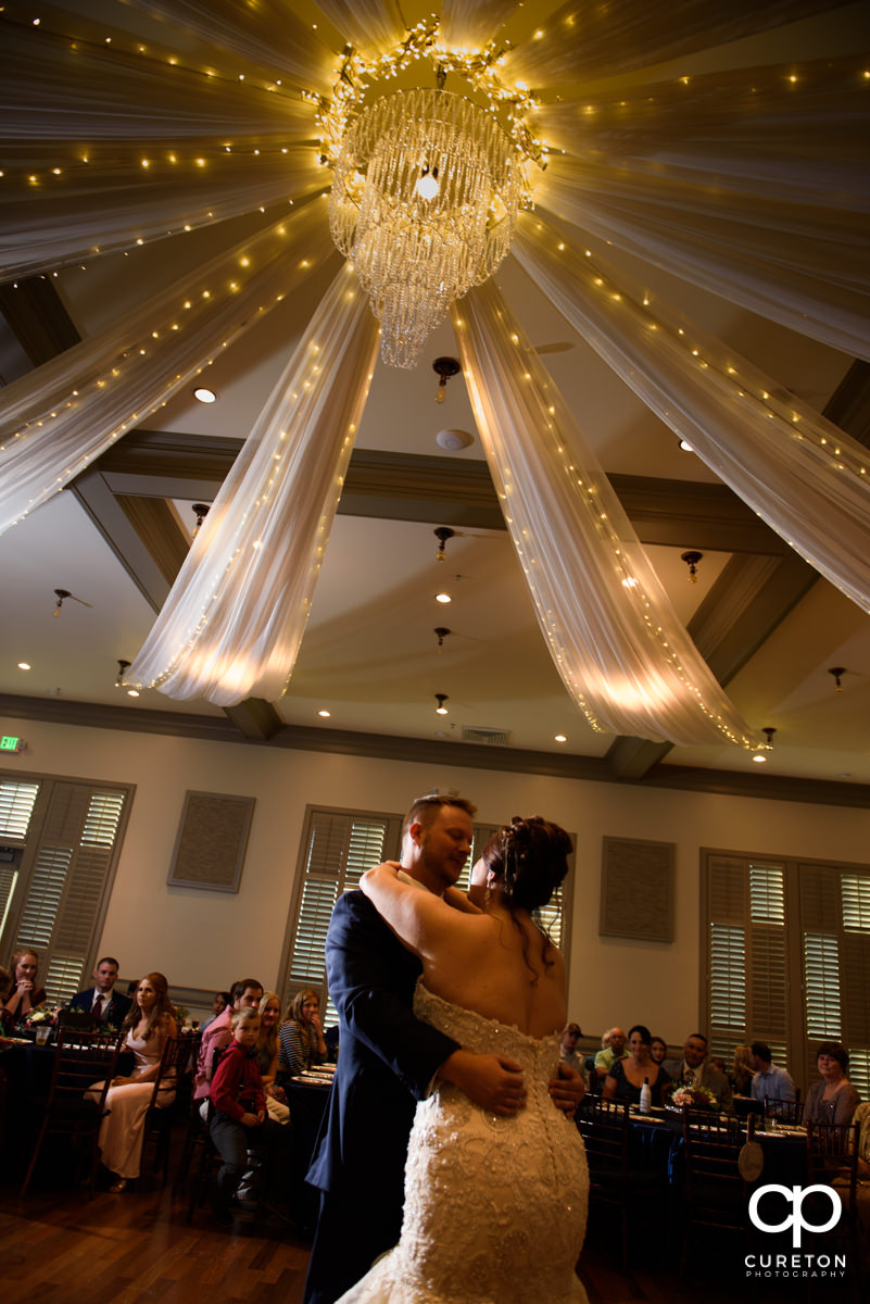Bride and groom share a first dance underneath a chandelier.