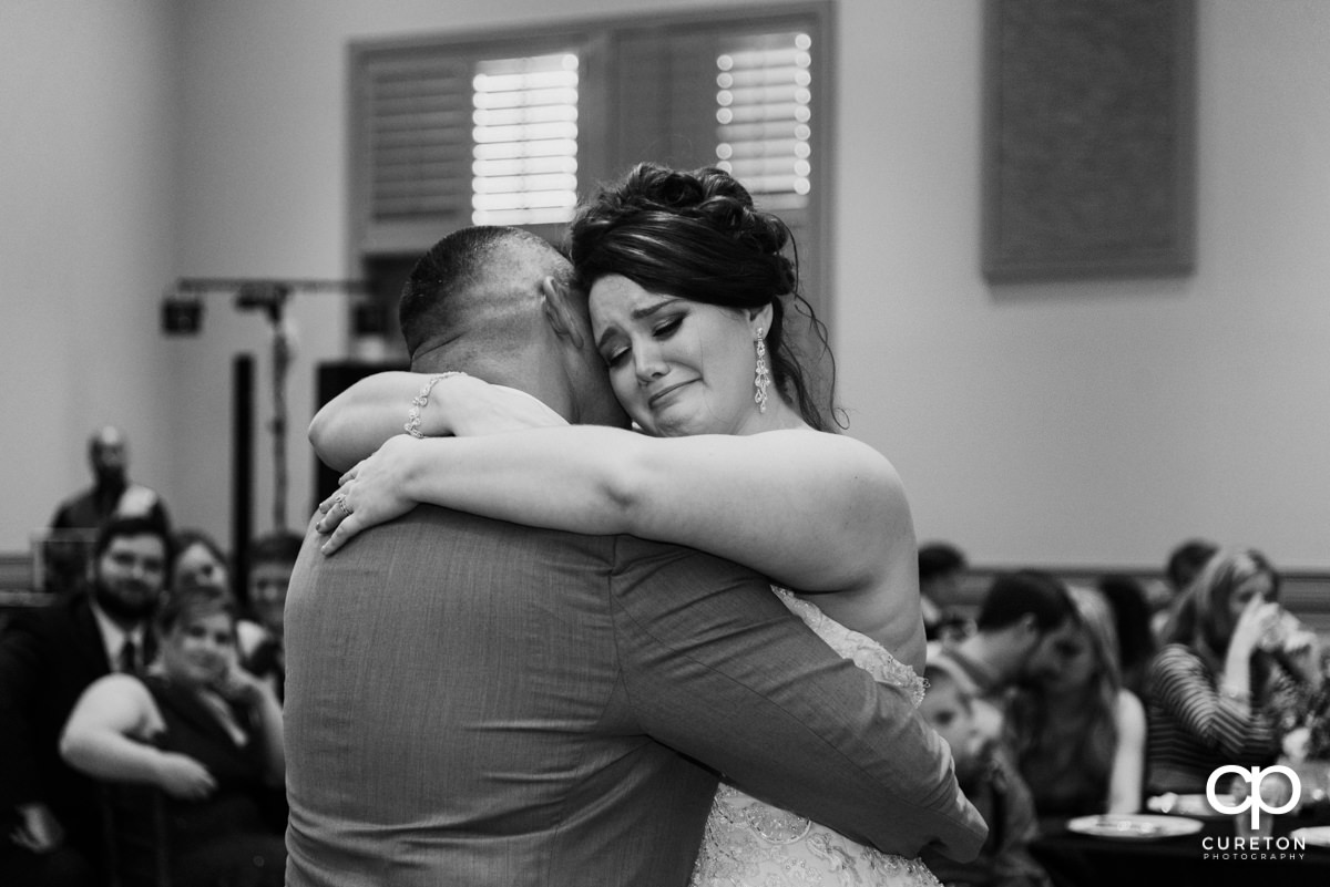 Bride crying after dancing with her dad at her wedding reception at Noah's Event Venue in Mauldin,SC.
