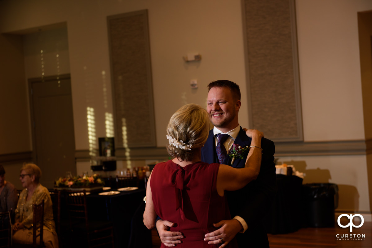 Groom smiling while dancing with his mother at the wedding reception.