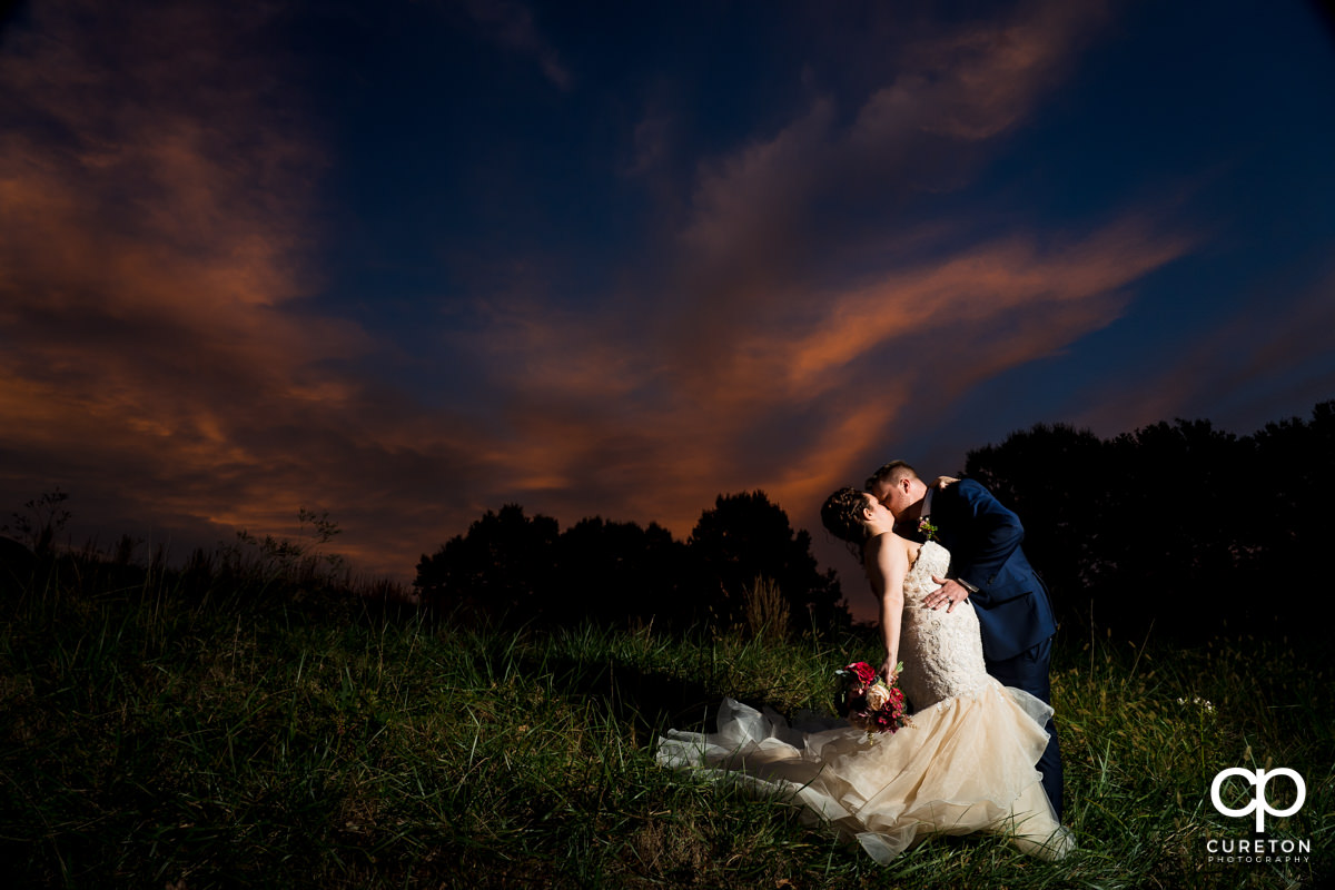 Groom dipping his bride at sunset after the wedding reception in Mauldin,SC.