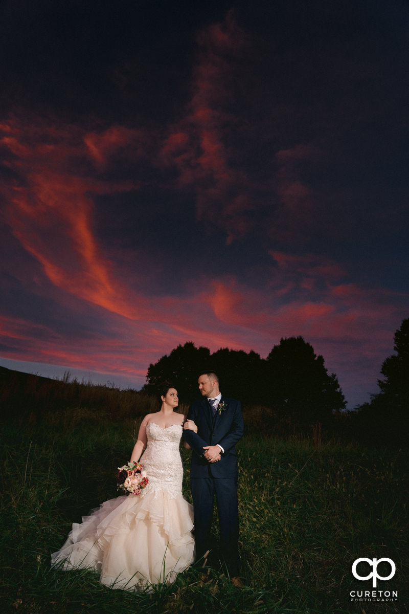Bride and groom arm in arm in a fiels at sunset at their Mauldin wedding.