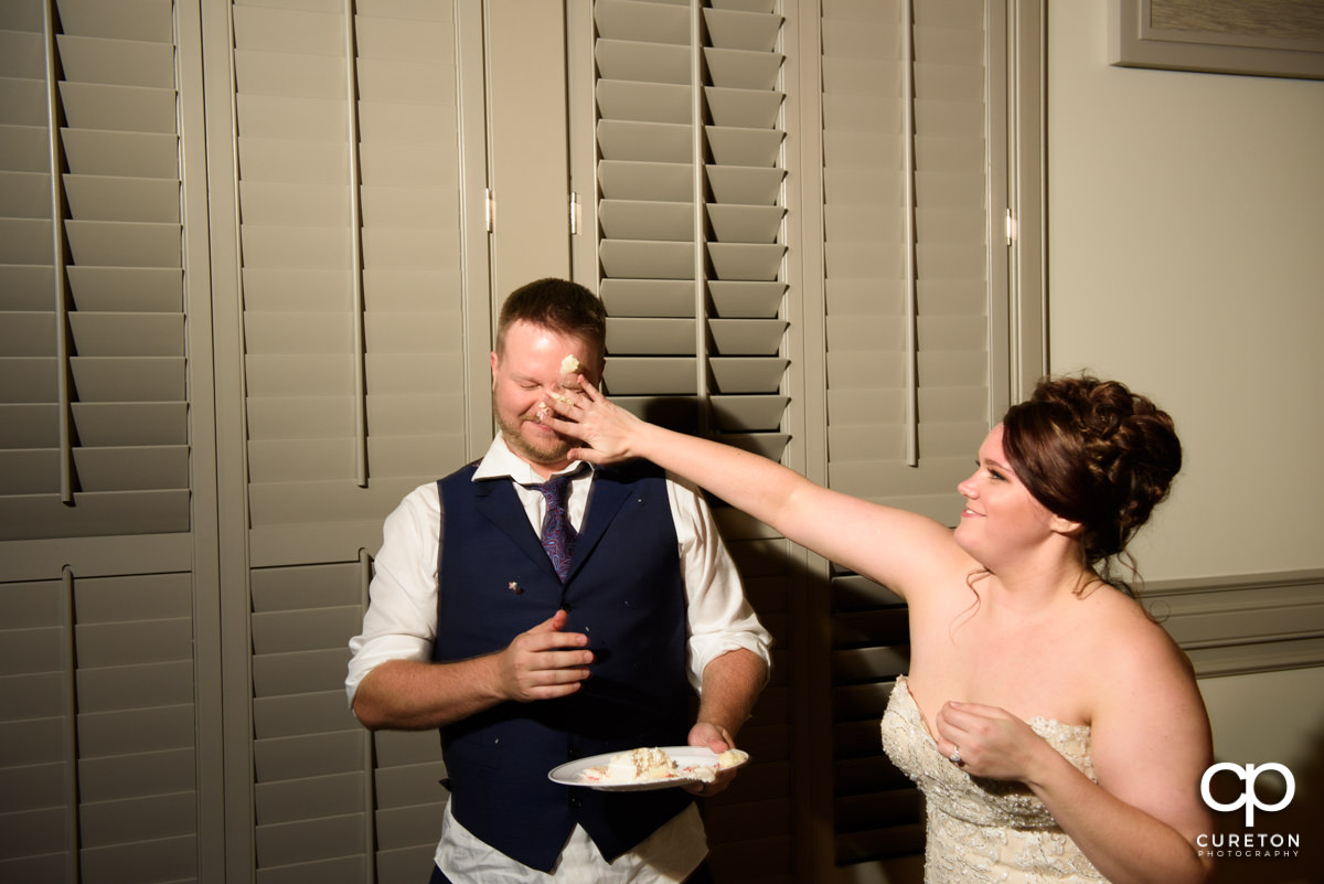 Bride smashing cake on the groom's face.