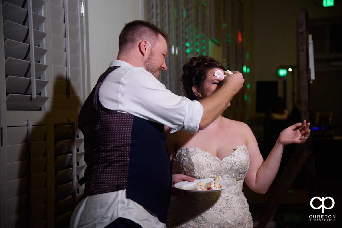 Groom smashing cake on the bride's face.