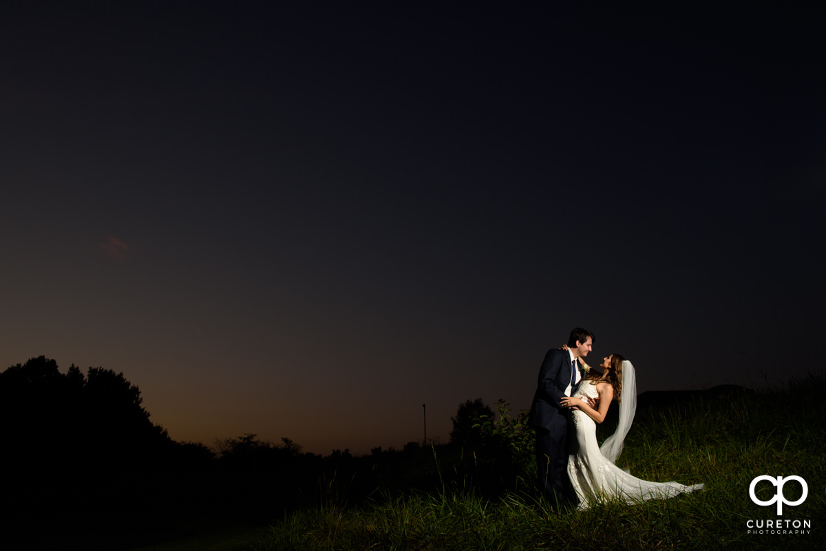 Brode and groom dancing at sunset after their wedding at Noah's Event Venue in Greenville,SC.