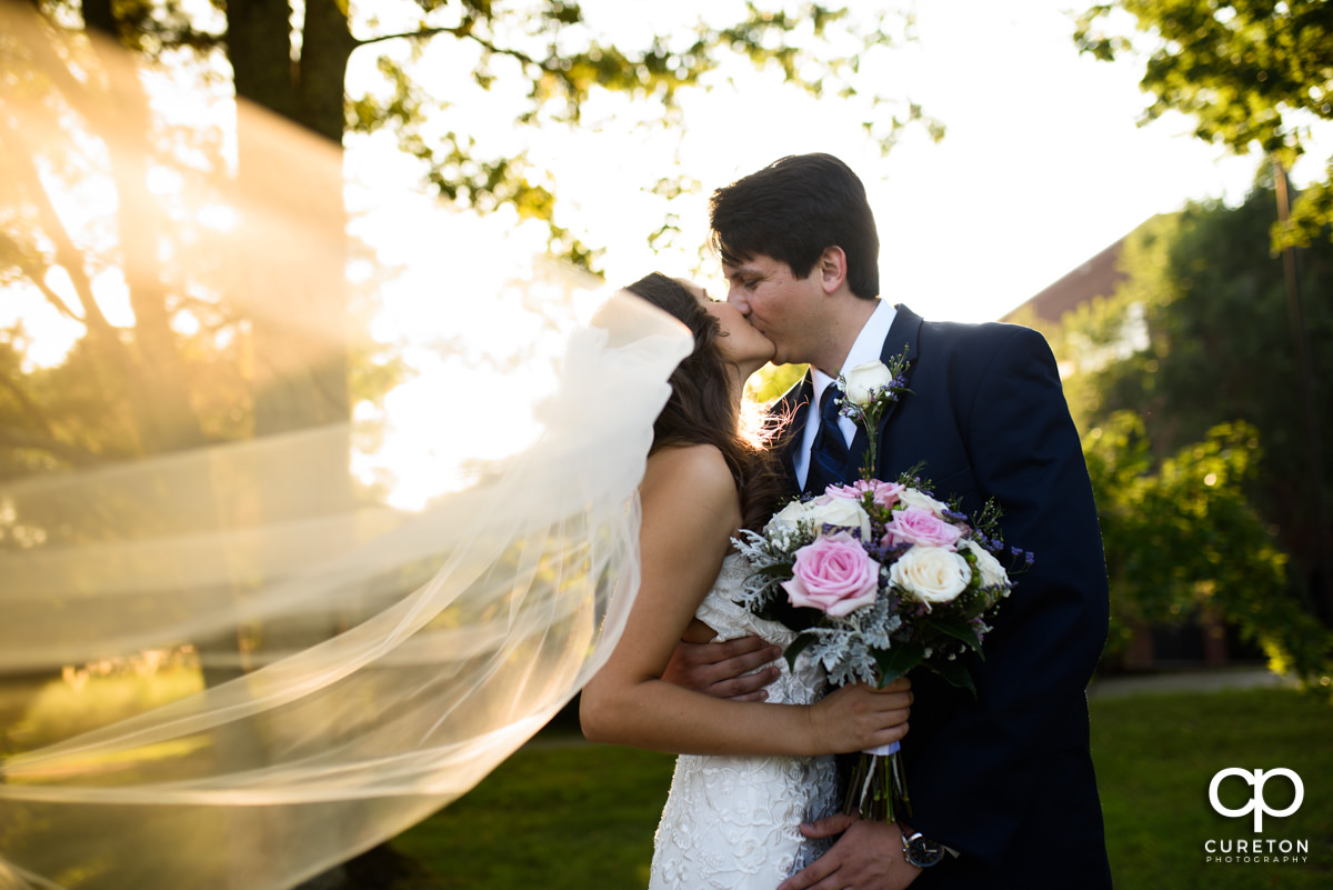 Groom kissing his bride dueing golden hour after their wedding at Noah's Event Venue in Greenville,SC..