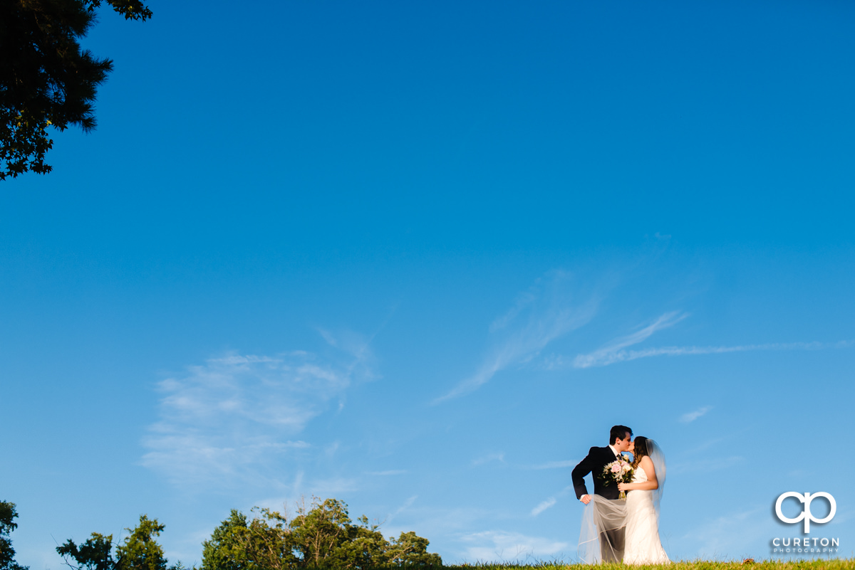 Groom kissing his bride on a hillside at Noah's Event Venue in Greenville,SC.