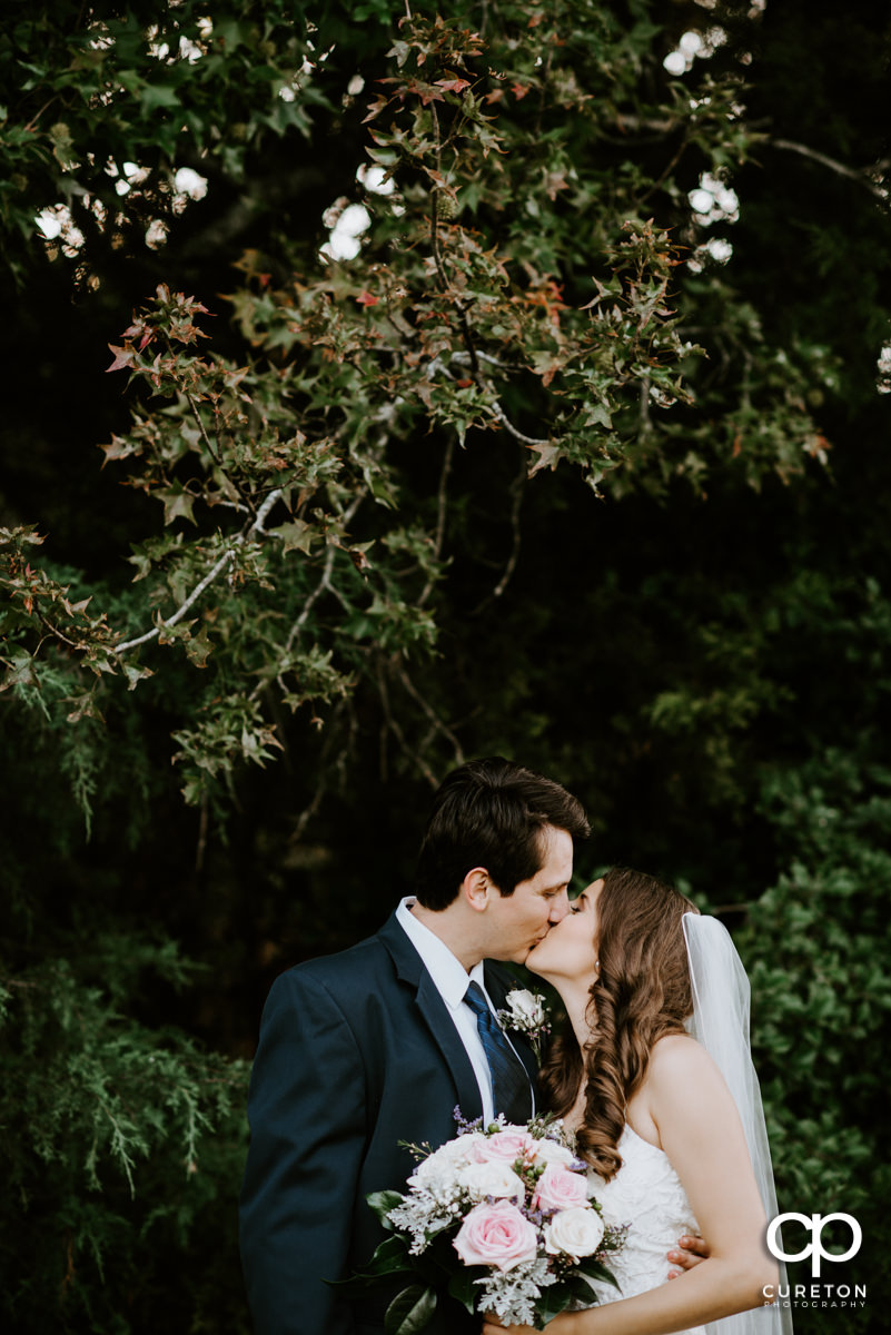 Bride and groom kissing out back after their wedding at Noah's Event Venue in Greenville,SC.