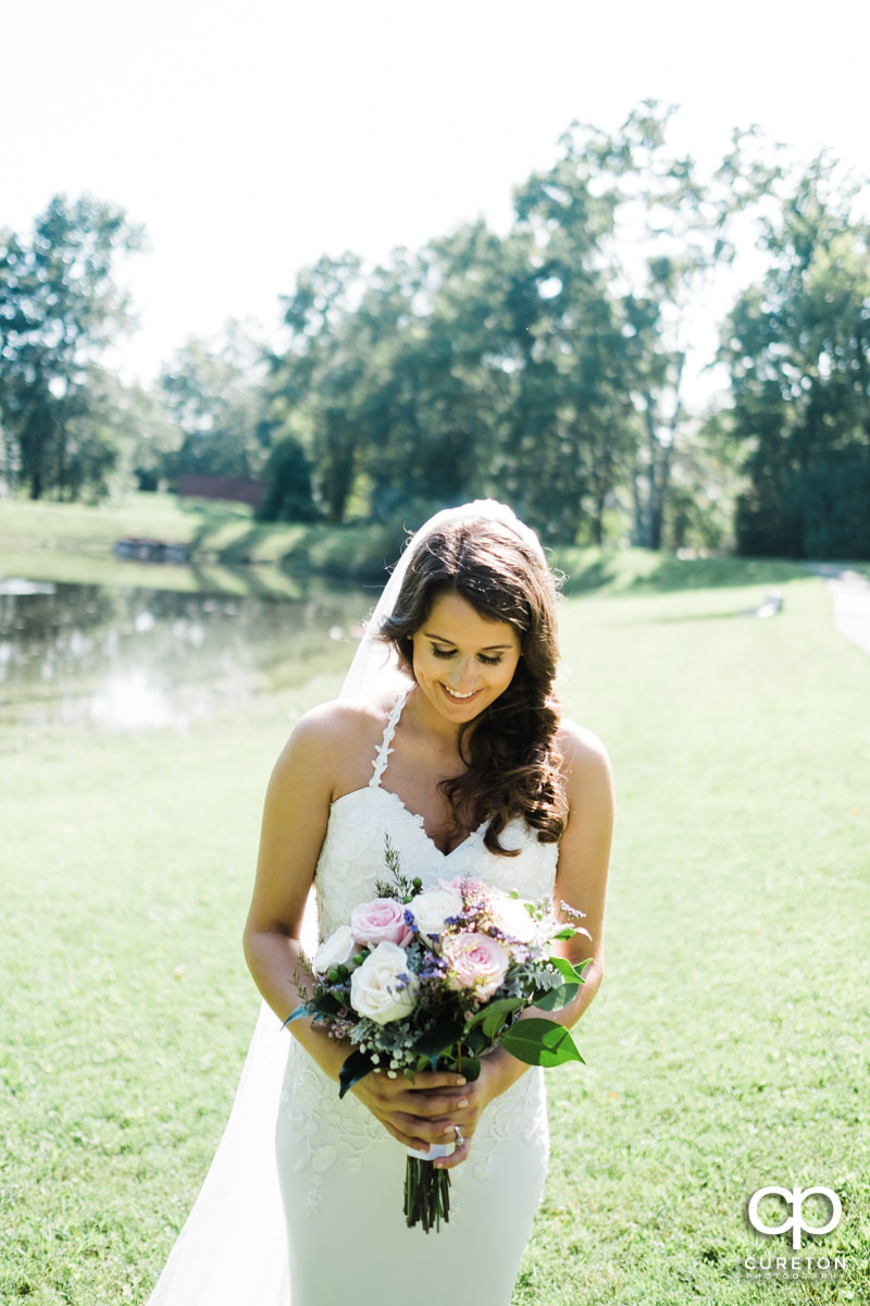 Bride looking at her flowers before her wedding at Noah's Event Venue in Greenville,SC.