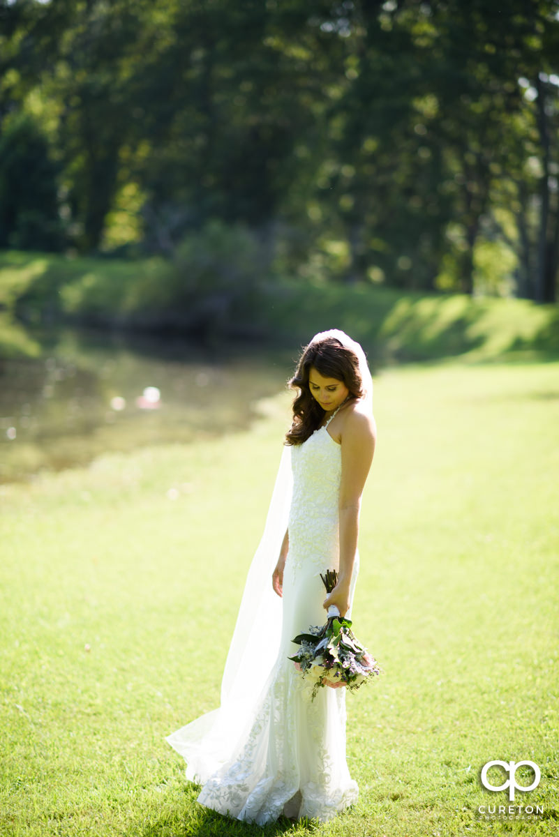 Bride standing beside a lake at Noah's Event Venue.