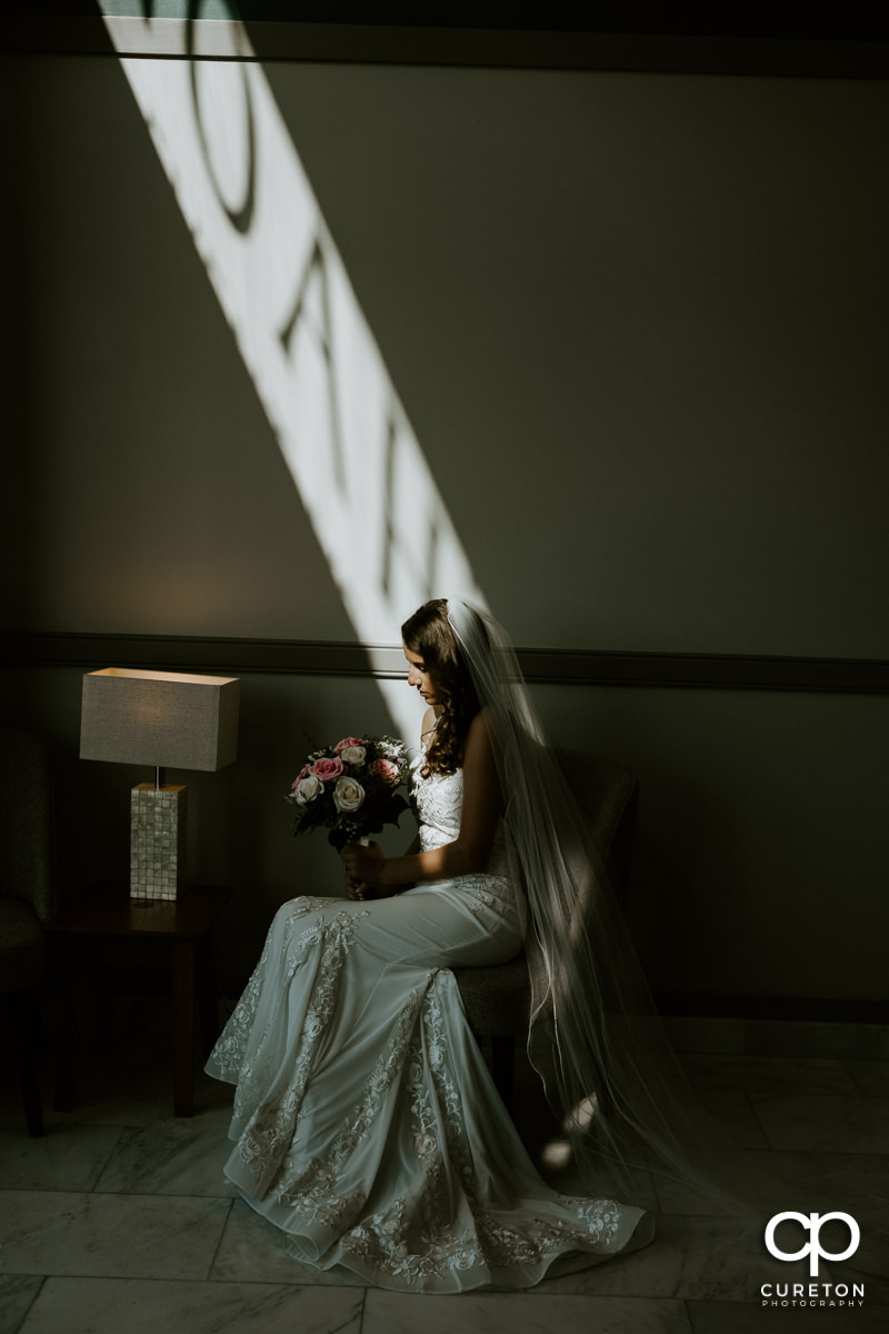 Bride sitting in a patch of light before her wedding.