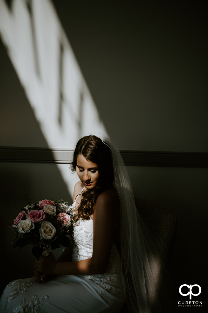 Bride sitting in a stream of light before her wedding at Noah's Event Venue in Greenville,SC.