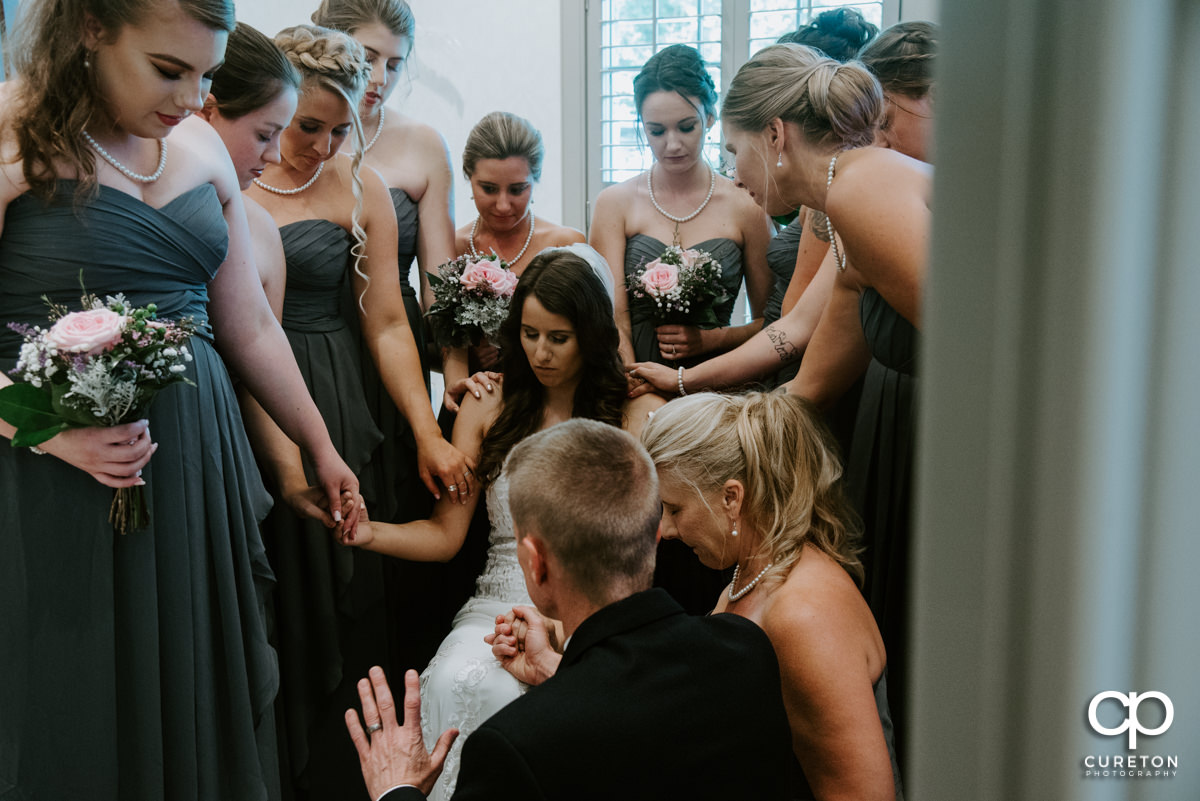 Bride and her bridesmaids praying.