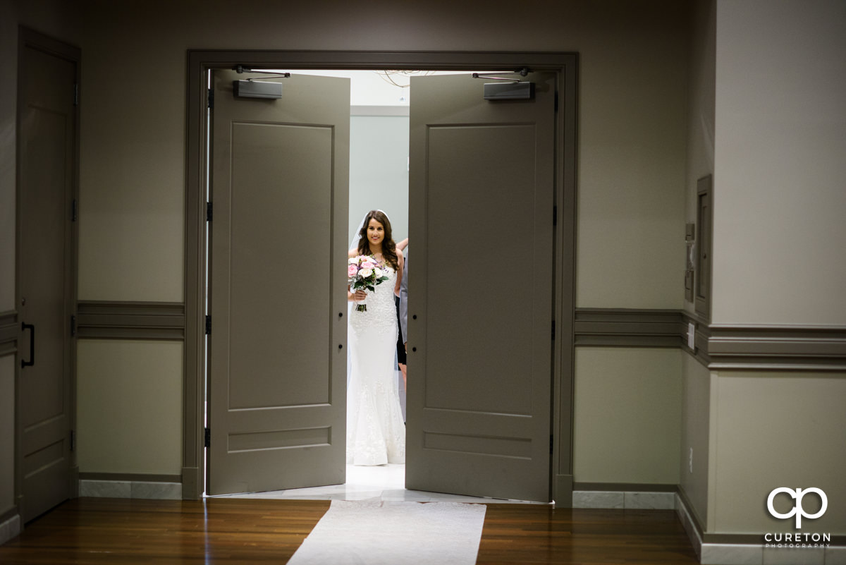Bride smiling as she makes her grand entrance down the aisle at Noah's Event Venue in Greenville,SC.