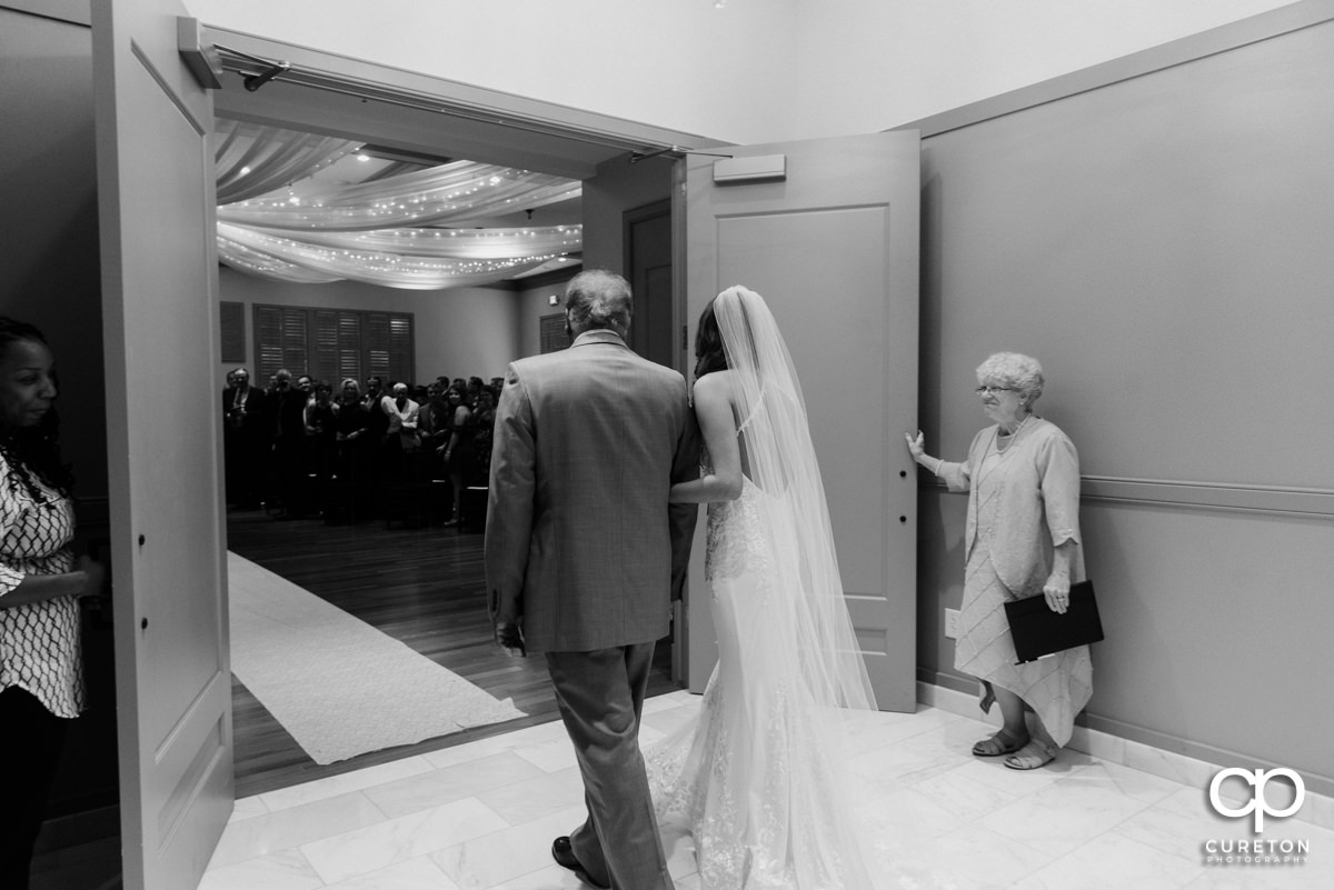 Bride and her father preparing to walk down the aisle.
