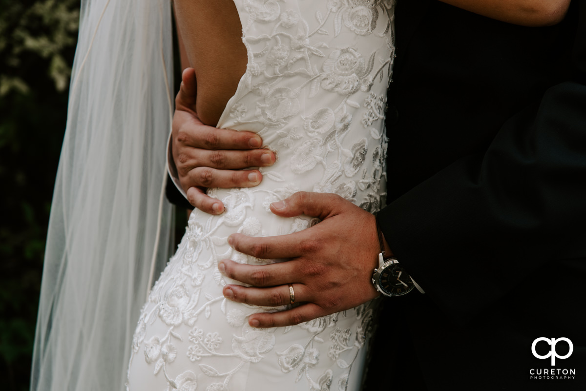 Closeup of groom's hands and ring as he holds his wife's waist.