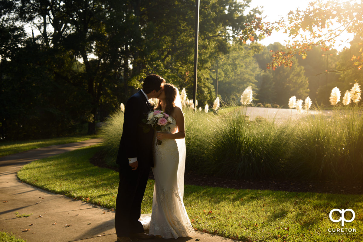 Bride and groom kissing in warm sunlight.