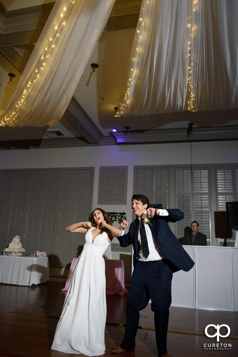 Bride and groom having a fun first dance at the reception.