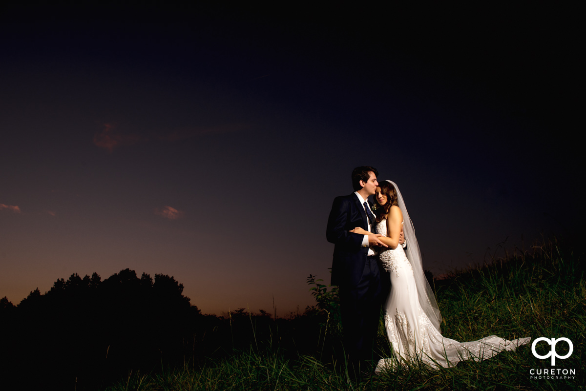 Groom kissing his bride on the forehead at sunset after their wedding at Noah's event venue in Greenville,SC.
