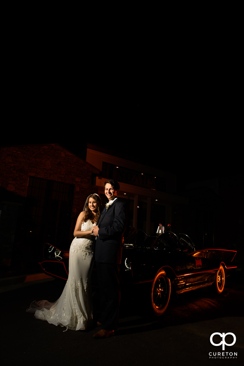 Bride and groom standing beside the batmobile.