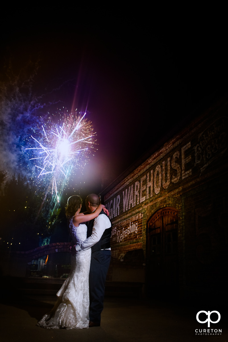 Epic photo of a bride and groom watching fireworks on the deck at their Old Cigar Warehouse wedding in downtown Greenville,SC.