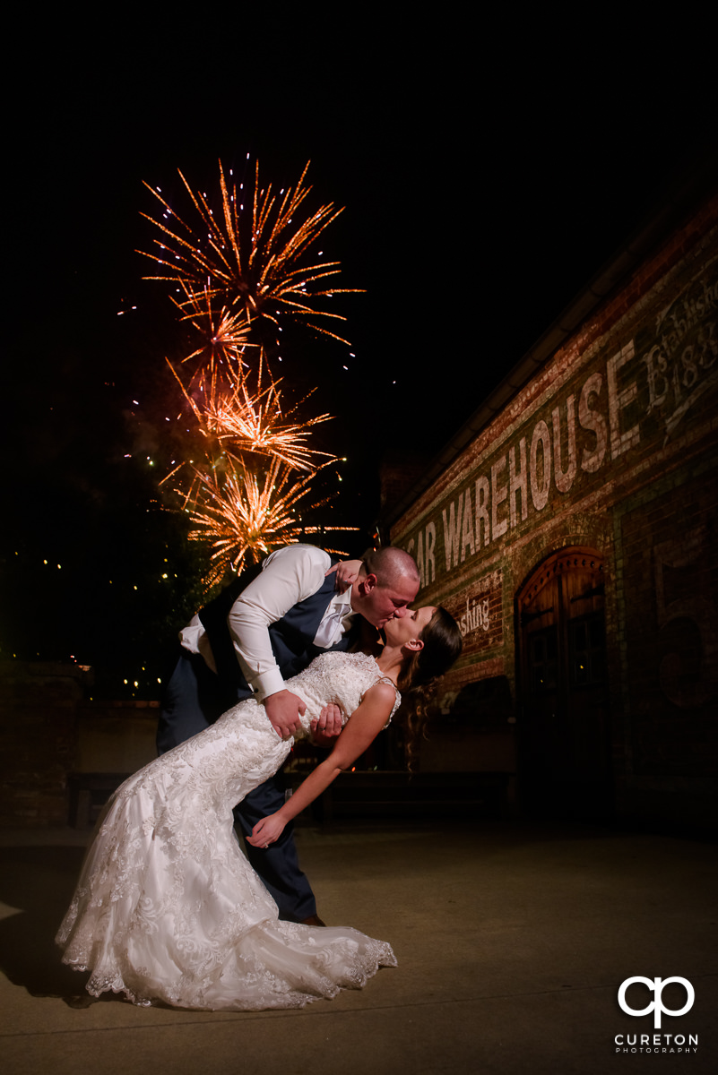 Couple dancing and kissing at their Old Cigar Warehouse wedding with fireworks in teh background from the Greenville Drive stadium.